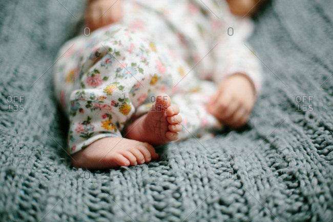 Toes of a newborn baby on a blue cable knit blanket