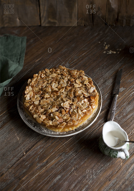 Almond caramel cake on plate on wooden background