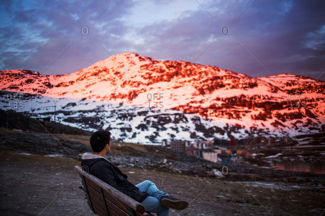 Man on bench over mountain town