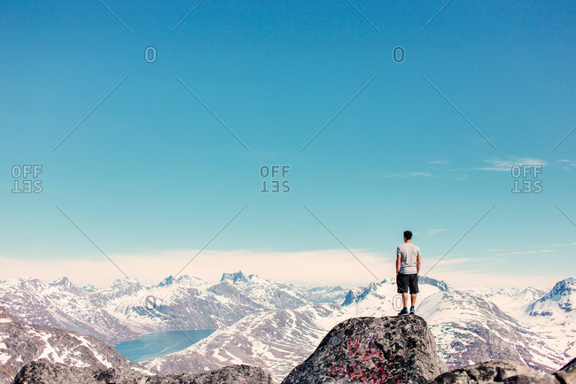 Man on summit of snowy mountain range