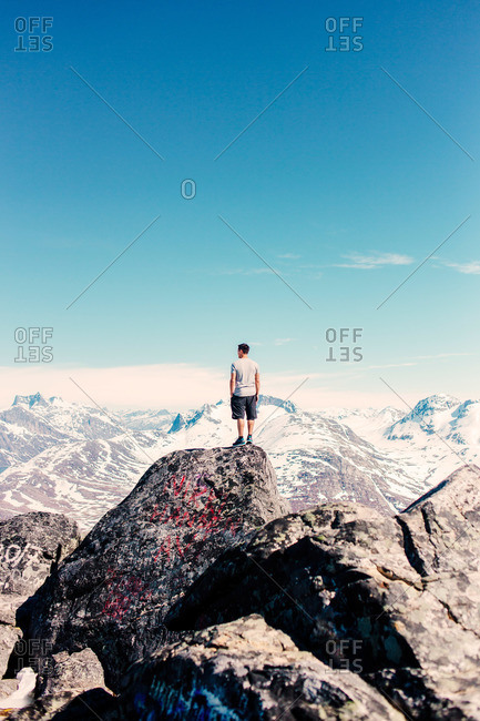 Man on summit in snowy mountain range