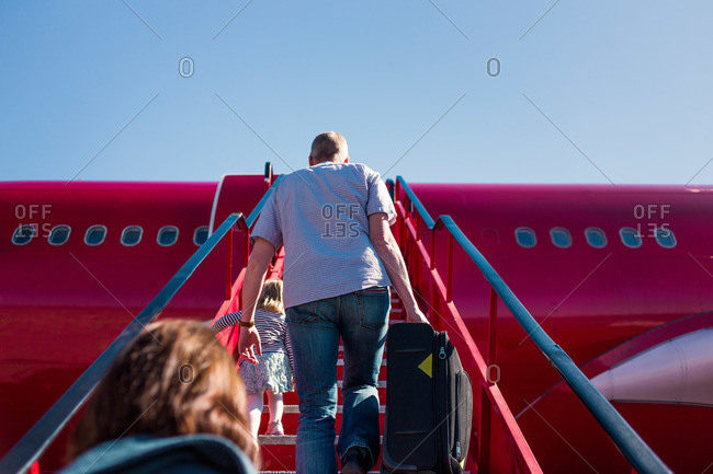People climbing steps to board plane