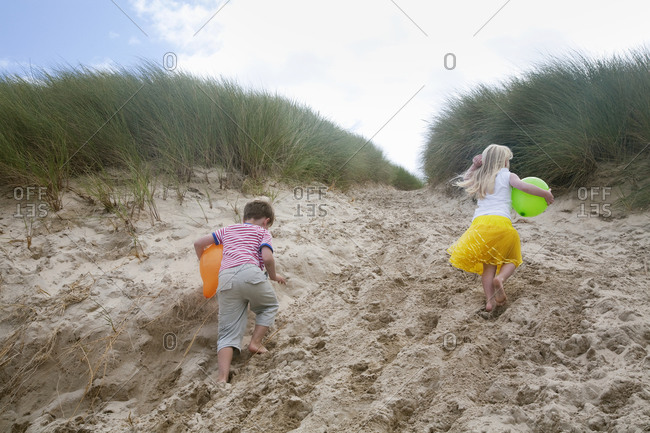 A boy and girl running though soft sand into the sand dunes.