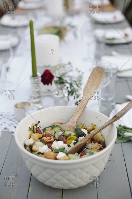 A bowl of salad on a table in a garden.