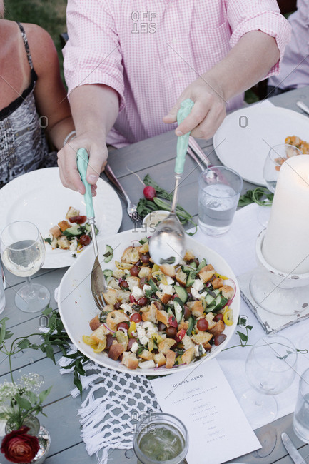 People around a table at a garden party, a bowl of salad.
