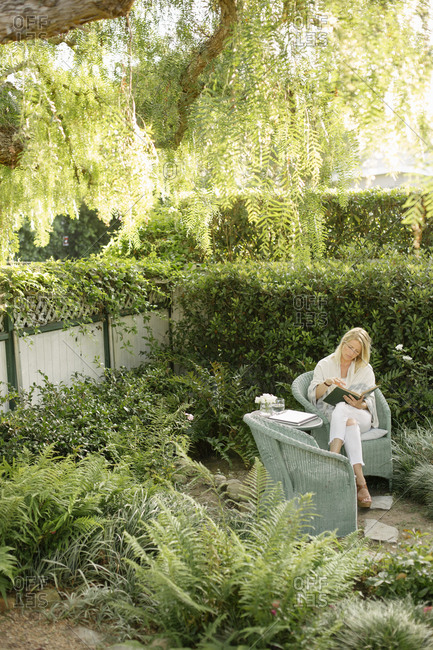 Blond woman sitting in a wicker chair in a garden, writing