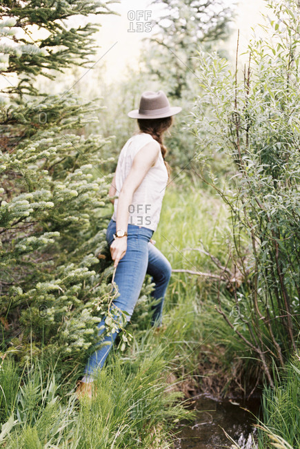 Woman wearing jeans and a hat walking through a forest.
