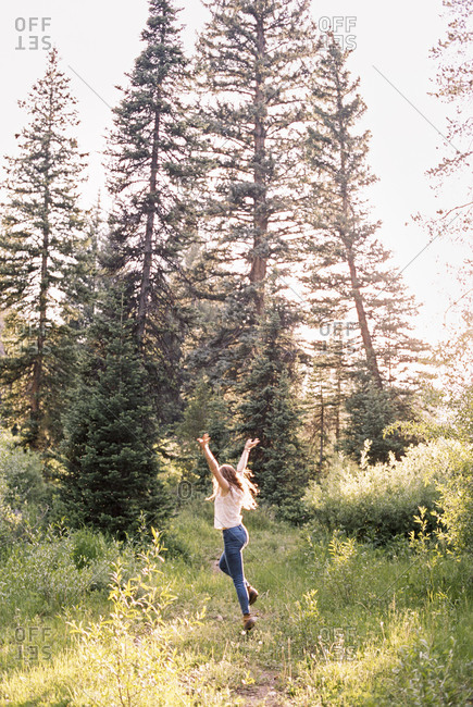 Woman jumping with joy in a sunlit forest.