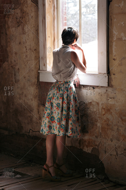 Woman in dress at window of old house