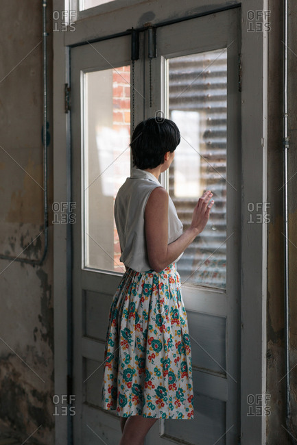 Woman in dress at door of old house