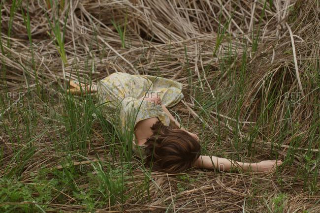 Woman in sundress lying in grass