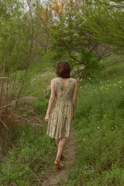 Woman in sundress walking in country