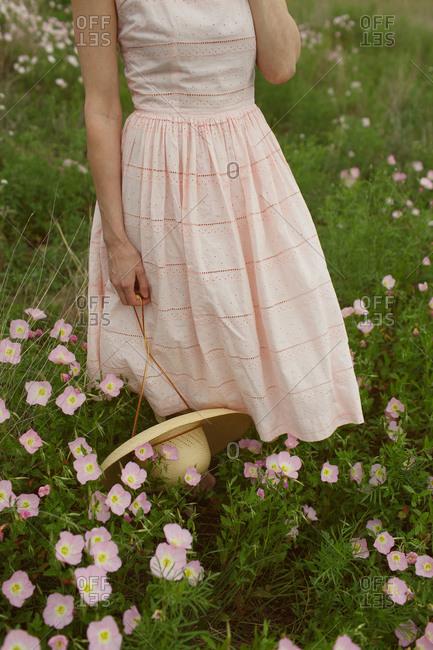 Woman in sundress standing in wildflowers