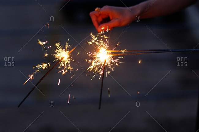 Woman lighting bundle of sparklers
