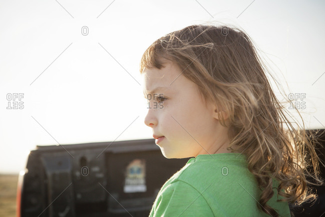 Closeup of young girl in profile sitting in back of pickup truck