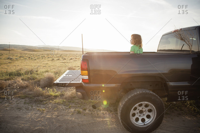 Young girl sitting in bed of pickup truck in rural landscape