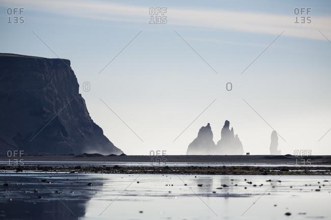 Three silhouetted horseback riders on beach at Reynisfjara with Reynisdrangar in the background