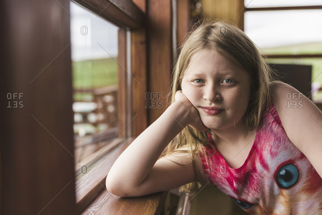 Portrait of young girl in kitten shirt leaning with elbow on windowsill