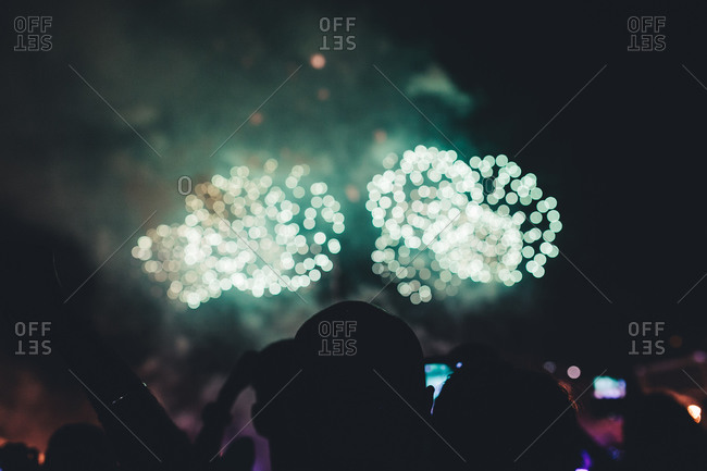 Crowd silhouetted by fireworks