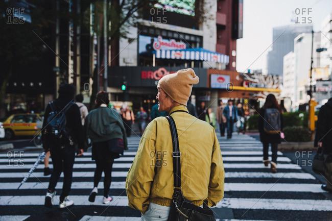 Tokyo, Tokyo - November 27, 2014: Man looking as he crosses a city street