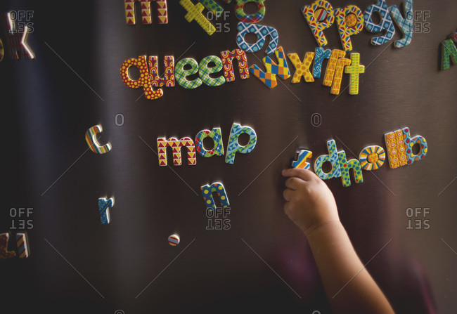Close up of a little girl playing with letter magnets