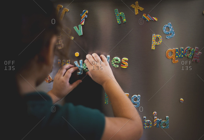 Close up of a girl playing with letter magnets