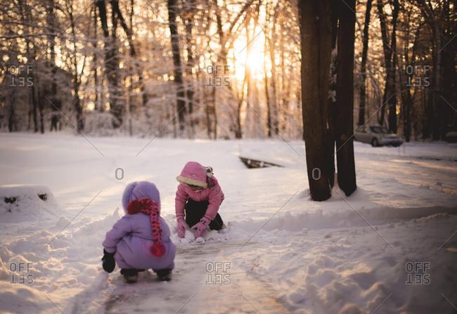 Two little girls making snow balls