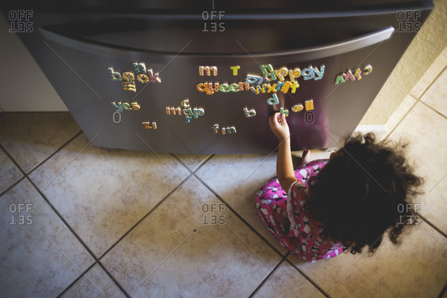 Little curly haired girl playing with letter magnets
