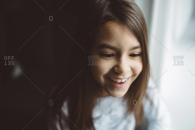 Smiling girl in portrait by sunny window