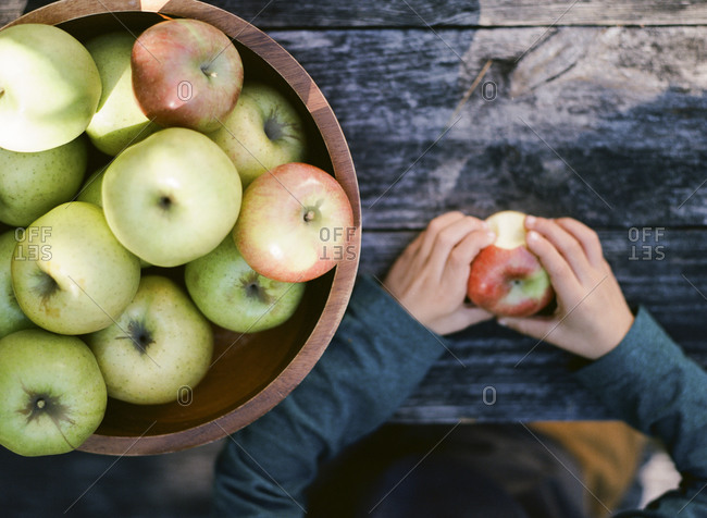 Boy holding apple with a bite out of it next to a basket of apples