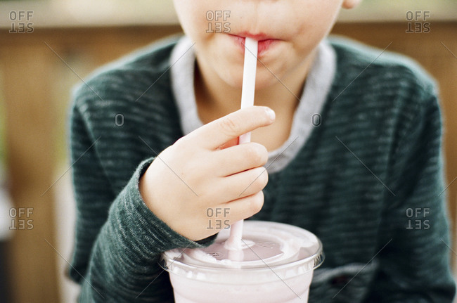 Close up of a boy drinking a milkshake