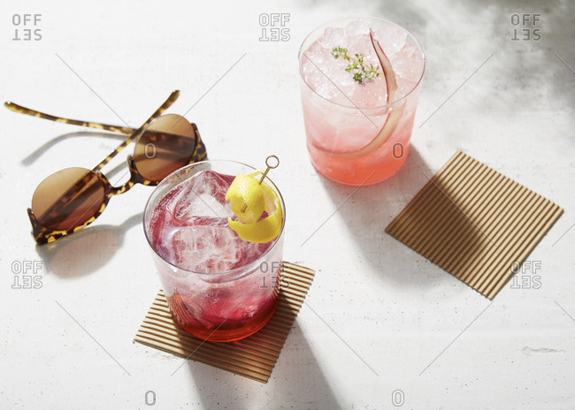 Two cocktails sitting on cardboard coasters by sunglasses
