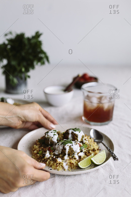 Curried lentil meatballs served on bulgur pilaf and topped with yogurt sauce are served by a woman