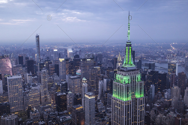 New York City, NY, USA - May 5, 2015: Aerial view of the Empire State Building illuminated with green light at night, Manhattan, New York City, NY