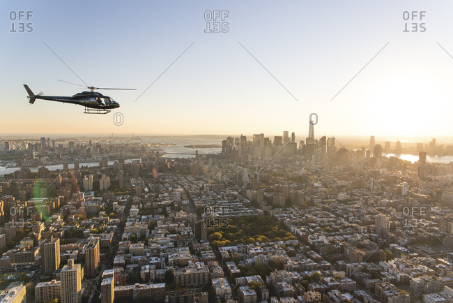 Helicopter flying over the island of Manhattan at sunset, New York City, NY