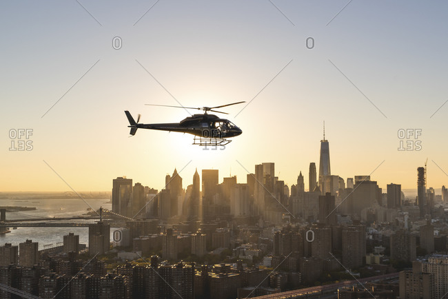 Helicopter flying above Manhattan at sunset, New York City, NY