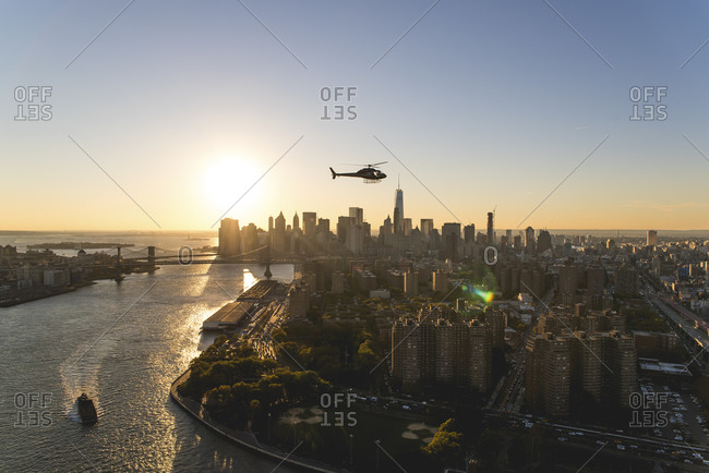 Helicopter flying over Manhattan at sunset, New York City, NY