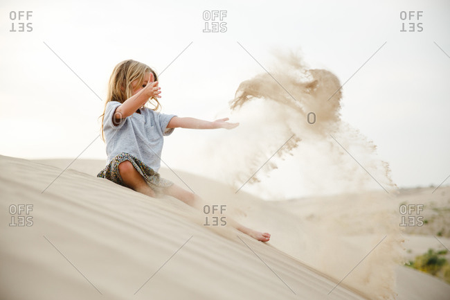 Young girl sitting on dune throwing sand in the air