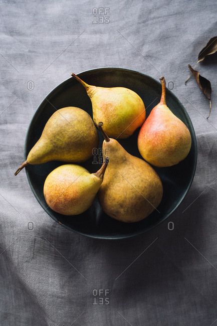 Five pears in a black bowl on linen tablecloth