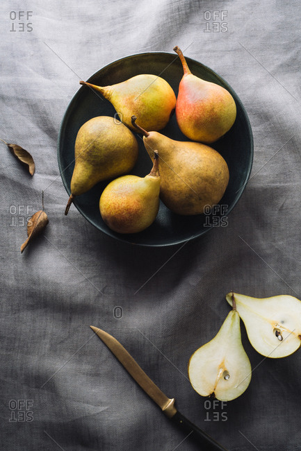 Sliced pear with knife and bowl of five pairs on linen tablecloth