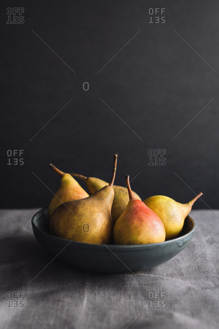 Still life of five pears in a black bowl