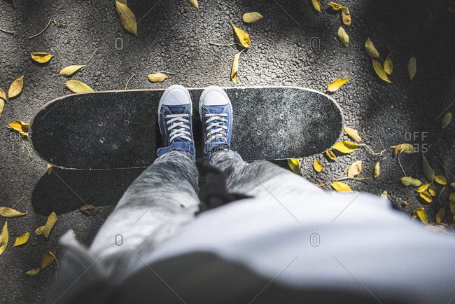 Boy standing on skateboard on path with autumn leaves