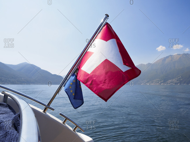 Boat with Swiss and EU flag on lake