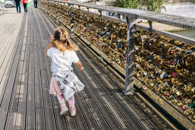 Girl on Parisian bridge by love locks