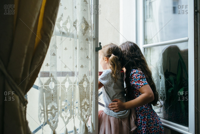 Girls looking out a Parisian window