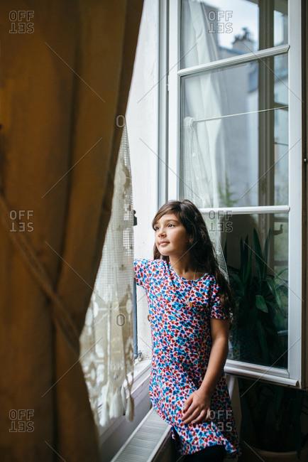Girl sitting in a Parisian window