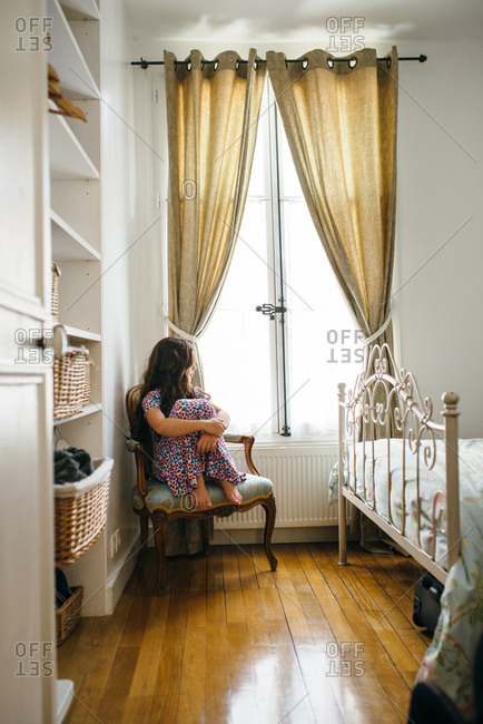Girl in chair looking out Parisian window