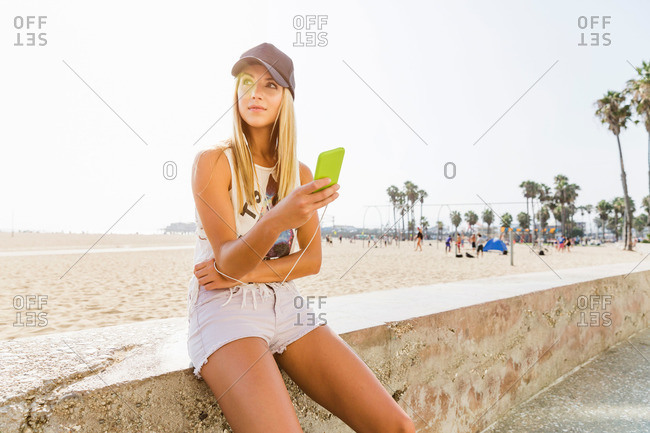 Woman with smartphone sitting by beach