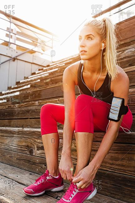 Female athlete adjusting trainers on steps