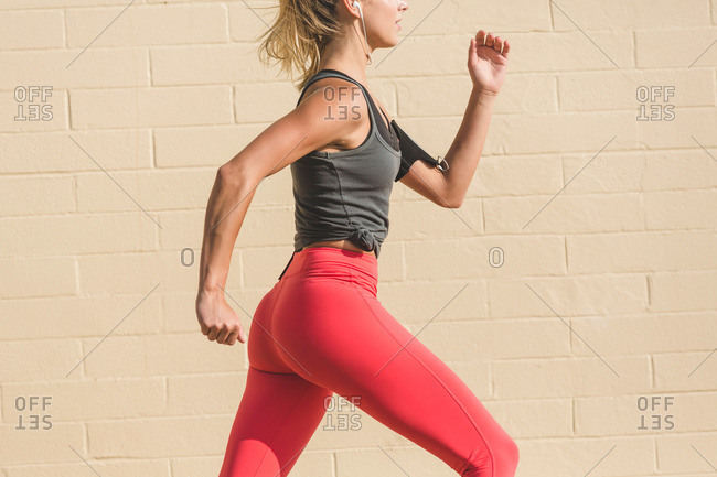 Female athlete running by wall